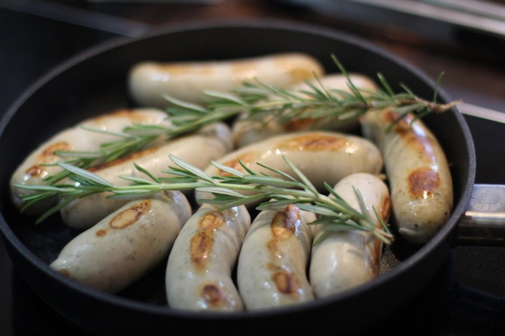 Stek pølsene med litt urter over